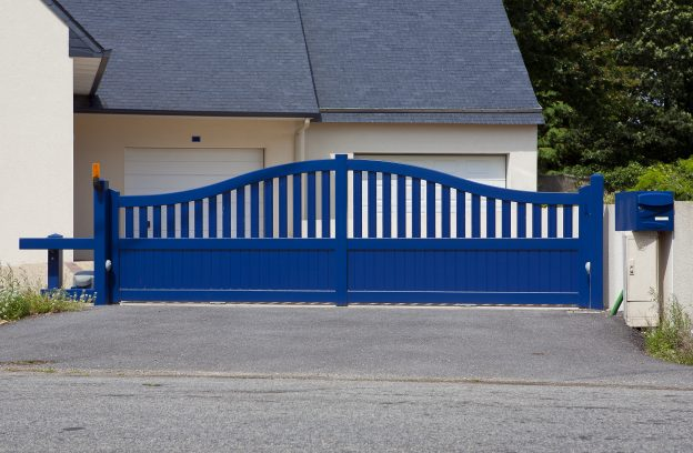 New family house with blue automatic gates in front of garage door. Picture is taken in Brittany , France and blue color is traditional. Automatic gate, also cantilever gate.